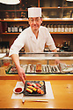 "Tokyo, Japan - Japanese Sushi Chef, Nogami Shinji serves a delicious-looking sushi dish : He established his own Sushi restaurant in 2001 called ""Nogami"" in the Hacchobori district of Tokyo. He started his career 25 years ago and continues to master the culinary craft to make the perfect sushi. His father, also a sushi chef, and his son who is currently in training to become a sushi chef shows illustrate how the art of making sushi has been passed down through generations. Nogami's day begins in the very early morning hours when he selects fish at the Tsukiji market. Choosing the best fish is considered the most important part of his work and he makes sure that he always has about 30 different varieties from which to serve. His restaurant is open late until 10pm and many regulars stay even later so Nogami will usually take an afternoon sleep break between 2pm-5pm when the restaurant is closed. ....Nogami-san's hobby is also fishing and he lives in the Tokyo Bay area so can do this in his free time. He usually releases what he catches though as he is worried that the Tokyo Bay water is not so clean. His son trains, works and sleeps at a different restaurant which is normal for a junior. As he improves his technique he will start to help more in his father's restaurant and eventually take over. There are no exams or text books for sushi chefs so this learning is all based on experience. Nogami's wife also helps out in the restaurant when she has time when their young daughter is at school.....Nogami often serves non-Japanese customers and he is surprised that ""They can eat anything and they often use heaps of wasabi"". He is proud of his ""Aritsugu"" knife which is worth about $700 and his most important tool. ....Nogami-san is worried that since the great March 11 earthquake and tsunami, the cost of fish has soared. (Photo by Yosuke Tanaka/AFLO)"