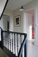 The staircase banister has been painted black in contrast with the white-painted floorboards and woodwork on the landing