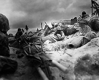 Marines take cover behind a sea wall on Red Beach #3, Tarawa.   November 1943.  (Marine Corps)<br /> Exact Date Shot Unknown<br /> NARA FILE #:  127-GR-119-64002<br /> WAR &amp; CONFLICT BOOK #:  1180