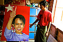 A member of NLD party exhibits a painting of Aung San Suu Kyi at a National League for Democracy (NLD) office. Nyaung U, Myanmar. 2012