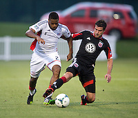 Chris Pontius (13) of D.C. United fights for the ball with Andrew Farrell (2) of the New England Revolution during the quarterfinals of the US Open Cup at the Maryland SoccerPlex in Boyds, Md.  D.C. United defeated the New England Revolution, 3-1.