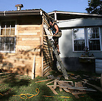 After working a variety of professions, ranging from jailer to custodian, an unemployed Charles Hobbs uses his free time to put siding on his new home in Beattyville Kentucky on Sept. 30, 2010. Photo by Matt Murray
