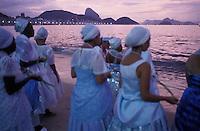 Offerings to Iemanja, the Sea Queen, Rio de Janeiro, Brazil. New Year celebration at Copacabana beach. Afro-brazilian women ( baianas from Umbanda religious rituals ) releasing palm flowers into the ocean.