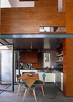 A bedroom has been created on the mezzanine above this modern open-plan kitchen
