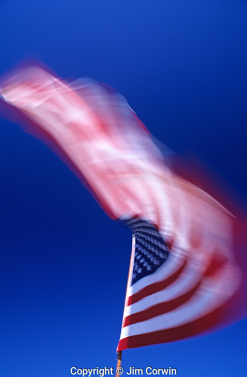 American Flag blurred waving in the wind with blue sky