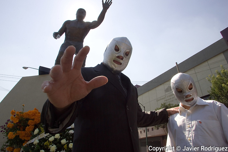 Mexican wrestler The Hijo del Santo, along with his child The Nieto del Santo, stand in front of the statue of The El Santo, a legendary wrestler in Mexico, as they pay homage during a ceremony in Mexico City, November 1, 2006 .  © Photo by Javier Rodriguez