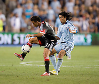 Marcelo Saragosa (11) of D.C. United keeps control of the ball in front of Roger Espinoza (15) of Sporting Kansas City during the game at Livestrong Sporting Park in Kansas City, Kansas.  D.C. United lost to Sporting Kansas City, 1-0.