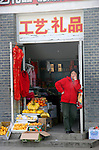 Asia, China, Beijing. Woman standing in Beijing Shop Doorway.