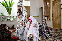 The female members of a family at their home where even the youngest girl wears a chador.