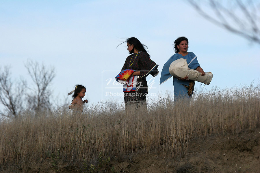 Two young ladies on top of a hill holding a blanket and a baby in a cradle with and a young boy running