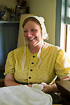 Old Bethpage, New York, U.S. 31st August 2013.  JOANNE SMITH of Deer Park is sitting next to a kitchen window in a building from the 1800's during the Olde Time Music Weekend at Old Bethpage Village Restoration. The yellow dress and white lace hat she is wearing are American Civil War era clothing, and the bowl of baked goods in front of her is covered with a white cloth.