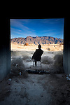 man sitting in  chair at the threshold of the manmade and the nautral landscape, conjuring notions of environmental contrast. taken near the sandia mountains of albuquerque, new mexico.