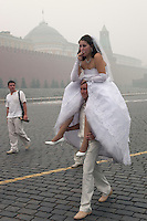 Moscow, Russia, 07/08/2010. .A bride smokes a cigarette as her groom carries her through Red Square in the worst smog so far in the record high temperatures of the continuing heatwave. Peat and forest fires in the countryside surrounding Moscow have resulted in the Russian capital being blanketed in heavy smog.