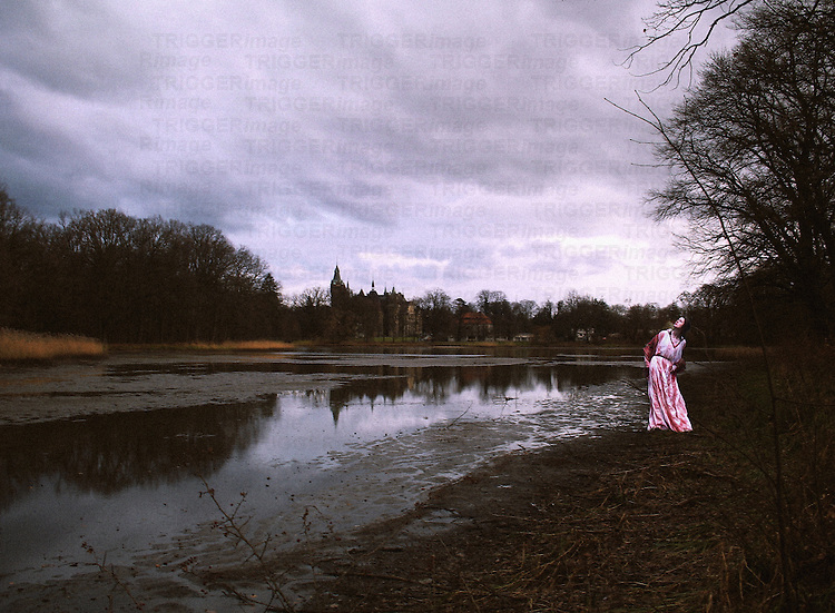 A woman in a long vintage gown, standing at a river bank on a stormy day, looking at the sky.