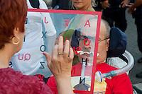 Roma 10 Luglio 2012.Manifestazione davanti al ministero dell'Economia del Comitato 16 Novembre, associazione di persone malate di Sla e loro famigliari, per chiedere il ripristino del fondo della non autosufficienza e gli assegni di cura. Un famigliare comunica con un ammalato di Sla con la Tavolo di Comunicazione.Rome, July 10, 2012.Demonstration at the Ministry of Economy, the Committee on November 16, an association of people with ALS and their families to demand the restoration of the fund of the not self-sufficiency  and care allowances. A family communicates with a patient with ALS  with the Table of Communication