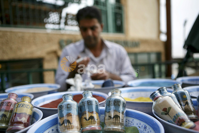 A Palestinian artist paints his paintings using colored sand in glass tubes,near West Bank city of Jericho , on Oct. 11.2010 . Jericho is one of the oldest continuously inhabited cities in the world, with evidence of settlement dating back to 9000 BC,it has a population of over 20,000 Palestinians. Situated well below sea level on an east-west route 16 kilometres (10 mi) north of the Dead Sea, Jericho is the lowest permanently inhabited site on earth . Photo by Eyad Jadallah