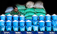 Rice Vendor waiting for customers and maybe checking the prices of rice futures on the net. (Photo by Matt Considine - Images of Asia Collection)