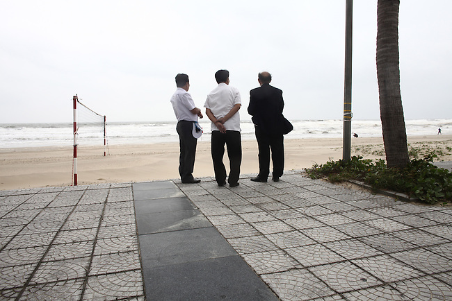 Men watch a winter storm brewing offshore in Da Nang, Vietnam. Dec. 23, 2012.