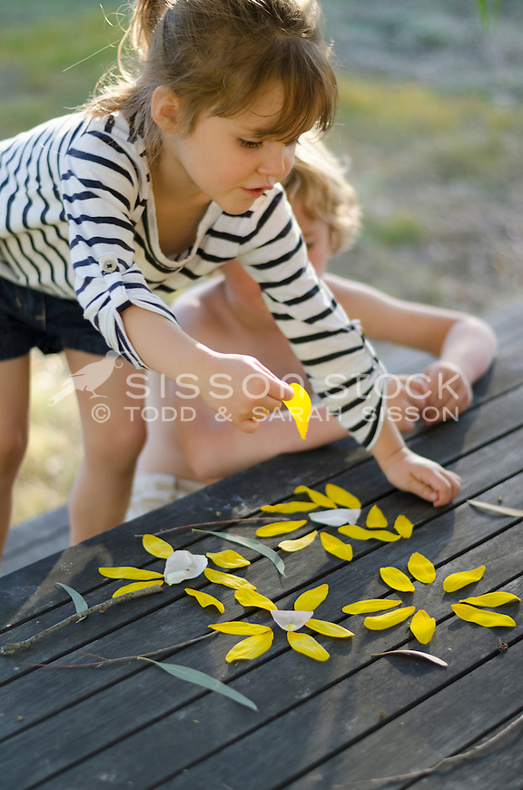 Young girl making flowers out of flower petals on a table outside in summer, New Zealand - stock photo, canvas, fine art print