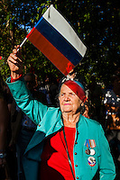 Moscow, Russia, 19/08/2012..A woman wearing a Boris Yeltsin badge waves a Russian flag at an opposition rally. Several hundred opposition demonstrators gathered near the Russian government White House to mark the 21st anniversary of the attempted coup in 1991 by Communist hardliners that led to the eventual break-up of the Soviet Union.