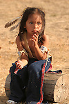 Young Native American boy sitting on a log looking distraught or upset