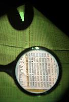 Giornale quotidiano economico e finanziario Sole 24ore con lente d'ingrandimento che evidenzia i titoli di borsa..Daily Economic and Financial 24h Sole with magnifying glass that highlighting stocks...