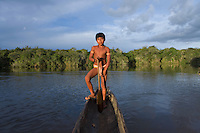 Xingu Indian boy in a dugout canoe, Amazon Basin, Brazil.