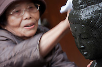 A woman washes the Arai kannon statue in an effort to cure sickness at Togan-ji temple in Sugamo, Tokyo, Japan. Tuesday, November 24th 2009. Sugamo is affectionately known as the old lady Harajuku, in reference to the Mecca for youth fashions in the South of Tokyo, and is a popular place for Tokyo's increasingly aged population.