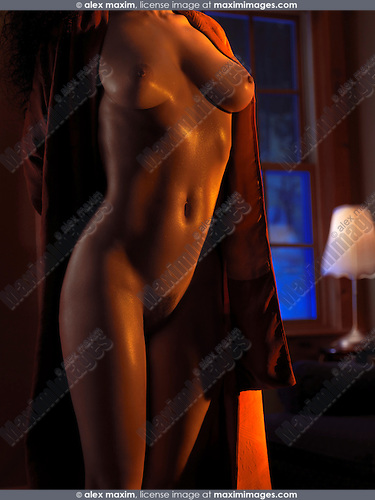 Sexy nude woman body with glittering skin in a dark room in dramatic light