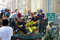 13 September 2001: Rescue workers hitch a ride on the back of a truck heading for ground zero following a Terrorist attack on the America's.  Lower Manhattan, NY. Area surrounding ground zero where the World Trade Centers WTC once stood only hours after they fell to the ground in New York.  Islamic terrorist Osama bin Laden declares The Jihad or Holy War against The United States of America on September 11, 2001. Headline news photos available for editorial use.