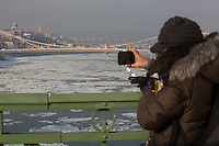 Woman takes photos of ice blocks floating on river Danube in Budapest, Hungary on January 10, 2017. ATTILA VOLGYI