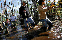 Everglades, Fla. -- Feb. 18, 2007 -- Maggie Hack, 11, right, a vacationer from West Bloomfield, Mich., leads her father, Joel, center, as they trudge through thigh-deep waters of a cypress tree stand while on a ranger-led swamp hike near the Oasis Visitor Center in the Big Cypress National Preserve just north of Everglades National Park on the southern tip of Florida on Sunday, Feb. 18, 2007.