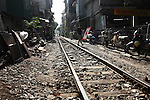 Residents walk along a rail line through a densely-populated neighborhood near the Old Quarter in Hanoi, Vietnam. Nov. 2, 2012.