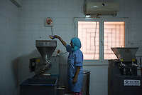 Morocco - Tidzi - Amina Hammoush, 40, pouring the argan nuts into the grinding machine. <br /> Modernisation has reached some of the cooperatives as well. At Ajddigue, women are paid by weight and to extract the kernels. The grinding and extraction of the oil is then processed by machines bought by the cooperative itself.