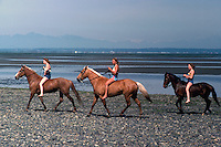 Teenage Girls horseback riding on Beach at Low Tide, along Pacific Ocean, BC, British Columbia, Canada