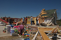 Rainsville, Alabama: Mandy Holcomb, right, walks across the remains of her front porch in this rural northeastern Alabama town Friday, where some residents say they feel overlooked. At least 32 people are confirmed dead across Rainsville and surrounding Dekalb County. (PHOTO: MIGUEL JUAREZ LUGO)
