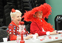 NWA Democrat-Gazette/FLIP PUTTHOFF <br /> THE COLOR OF FUN<br /> Joyce Parks (left) and Shirley Jordan laugh at clever words of wisdom read Wednesday Feb. 15 2017 during the Rogers Red Hat Hotties valentine party at the Rogers Adult Wellness Center. The ladies enjoyed a potluck lunch and camaraderie during their montly get together. The group gets together once a month for lunch, games and trips around the region. The Red Hat Society is worldwide and open to women 50 and over with a mission of having fun and enjoying life.