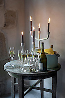Contemporary candelabra on a rustic garden table illuminate a corner of the orangery