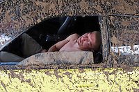 Moscow, Russia 12/07/2008..A competitor sleeps in his mud-spattered vehicle at the annual Autoexotica Show, a ten day festival that attracts thousands of Russian motor enthusiasts. Figures show the Russian auto market has just overtaken Germany's to become the largest in Europe, and analysts predict that within four years it will be the third largest in the world.