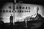 Man stands mesmerized in front of wall advert, Shanghai, China.
