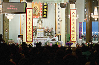 Christmas mass in the Wangfujing Church (Dongdang). This church belongs to the official Church but drains catholics of the hidden chucrch as well, specially for important celebrations. On the left side a digital apnel with the text of the prayers for the numerous new believers. December 24 2009.<br /> <br /> (French) Messe de Noel dans l'&quot;Eglise de l'Est&quot; &agrave; P&eacute;kin, dont le clerg&eacute; d&eacute;pend du gouvernement. A gauche la r&eacute;f&eacute;rence des chants et les paroles pour les nouveaux fid&egrave;les. 2009 -