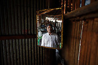 """U Mon Gyit, a 35 year old Muslim Burmese refugee is reflected in the mirror at his food shop at the Mae La refugee camp near Mae Sot June 3, 2012. Asked about Aung San Suu Kyi's visit to the camp U Mon Gyit said """"I saw her yesterday. We are only small people, we don't know can she make changes or not. But, even if she becomes the president I will still watch situation for years before deciding to go back."""" Myanmar's pro-democracy leader Aung San Suu Kyi visited on Saturday Mae La, the biggest refugee camp along the Thailand-Myanmar border where tens of thousands of her compatriots found shelter after escaping from Myanmar.  REUTERS/Damir Sagolj (THAILAND)"""