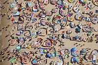 People swim and sunbathe on a crowded beach.