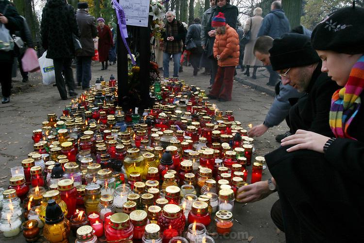 Ewa Ledochowicz family on All Saints Day. Lodz, Poland. Borys and Olga light candles.