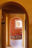 View through a series of archways to a cane-backed chaise-longue which sits beneath a small window