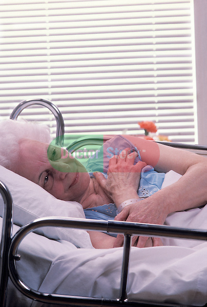 elderly woman lying in hospital bed with worrying, dazed look