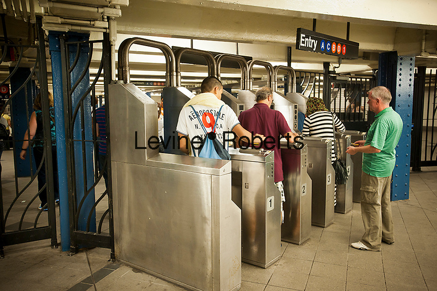 Straphangers enter the subway via turnstiles at the Columbus Circle station in New York on Sunday, September 4, 2011. The turnstile on the left (closest to the camera) is the most used turnstile in the city's transit system seeing 1,402,766 users in the year ending August 19. The turnstile is the first entrance upon descending the escalator at this particular Columbus Circle access. Runners-ups are in the Jamaica Station  and Times Square and Grand Central Station.  (© Richard B. Levine)