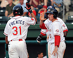 First baseman Christian Vazquez (15), right, high-fives outfielder Reymond Fuentes (31) after both scored against the Augusta GreenJackets in a game on May 20, 2010, at Fluor Field at the West End in Greenville, S.C.