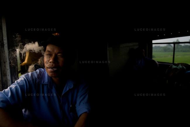 A train worker takes a smoke break from Hanoi to Sapa, Vietnam.