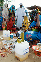 Sudan. West Darfur. Kerenek. Each friday is market day Women, wearing colorful veils on the heads, sit on the ground and sell their producst to customers, like a bottle of oil. Some more oil is stocked is a plastic jerrycan given by UNICEF.  © 2004 Didier Ruef